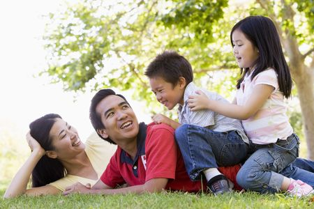 countryside loving: Family lying outdoors being playful and smiling