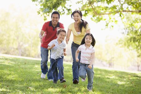 happy asian family: Family running outdoors smiling Stock Photo