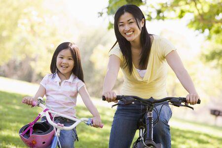 ni�os en bicicleta: Mujer y ni�a en bicicletas sonriendo al aire libre