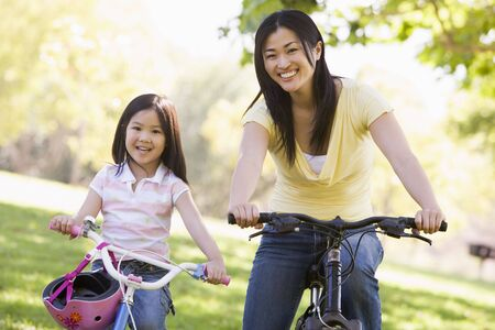 helmet bike: Woman and young girl on bikes outdoors smiling Stock Photo