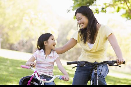 Woman and young girl on bikes outdoors smiling photo