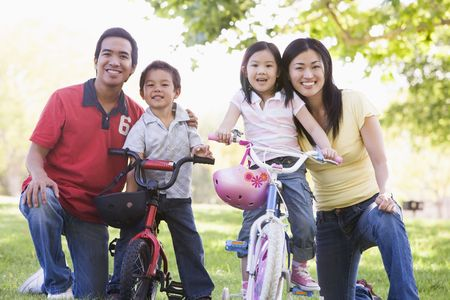 healthy asian family: Family with children on bikes outdoors smiling