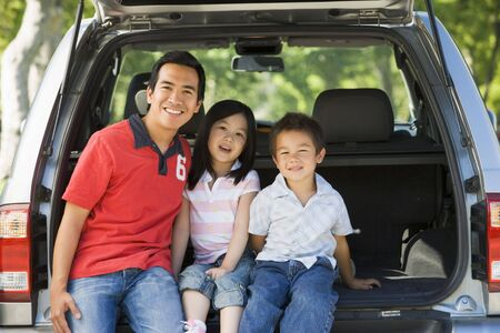 man driving: Man with two children sitting in back of van smiling