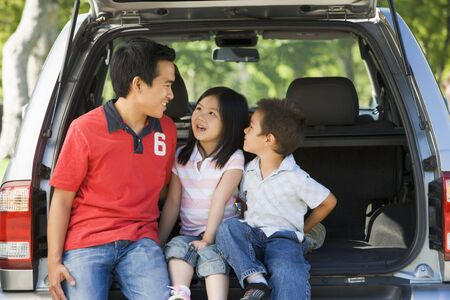 Man with two children sitting in back of van smiling photo