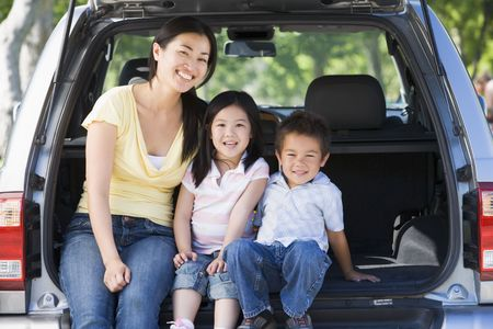 bambini seduti: Donna con due bambini seduti sul retro del furgone sorridente Archivio Fotografico