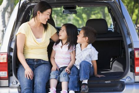 Woman with two children sitting in back of van smiling Stock Photo - 3475245