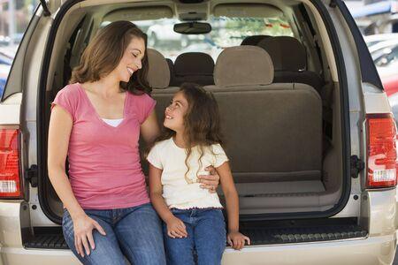 Femme avec jeune fille assise à l'arrière du van sourire