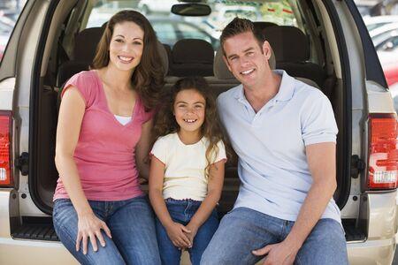 car carrier: Family sitting in back of van smiling