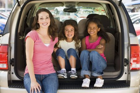 Woman with two young girls sitting in back of van smiling photo