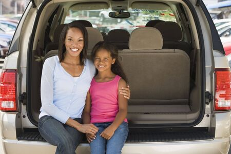 Woman with young girl sitting in back of van smiling photo