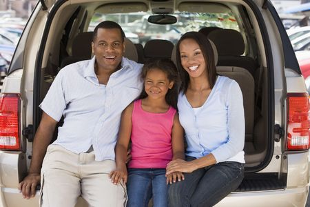woman driving car: Family sitting in back of van smiling