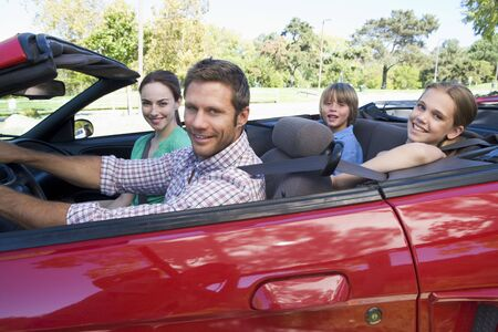 new motor car: Family in convertible car smiling Stock Photo