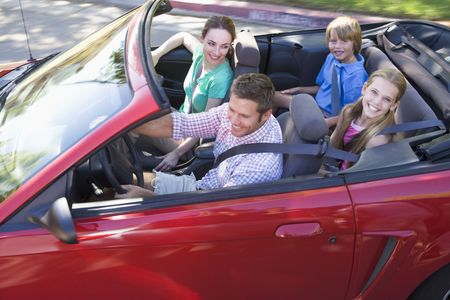 convertible car: Family in convertible car smiling Stock Photo