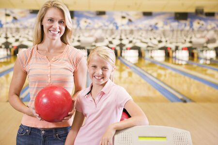 bowling: Woman and young girl in bowling alley holding ball and smiling
