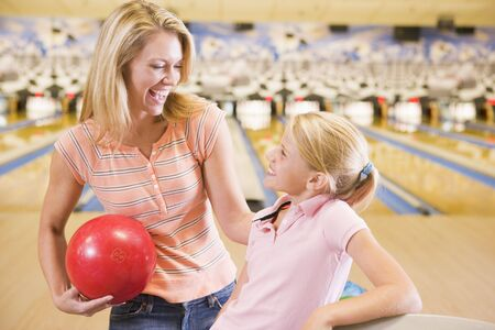Woman and young girl in bowling alley holding ball and smiling photo