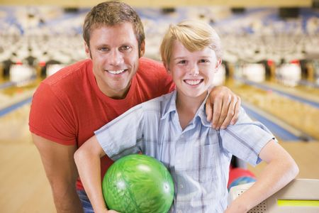 bowling alley: Man and young boy in bowling alley holding ball and smiling Stock Photo