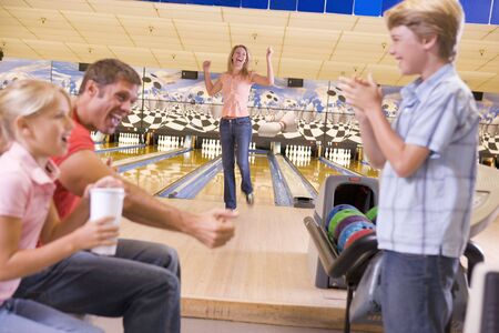 girls night out: Family in bowling alley cheering and smiling Stock Photo