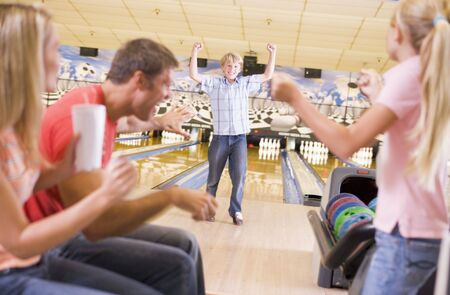 Family in bowling alley cheering and smiling photo