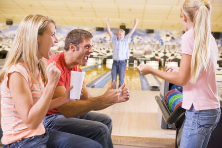 bowling alley: Family in bowling alley cheering and smiling Stock Photo