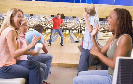bowling alley: Family in bowling alley with two friends cheering and smiling