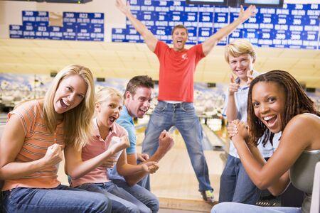 due amici: Family a bowling con due amici e sorridente cheering
