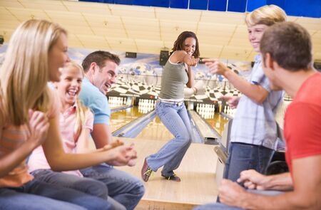 in bowling alley with two friends cheering and smiling photo