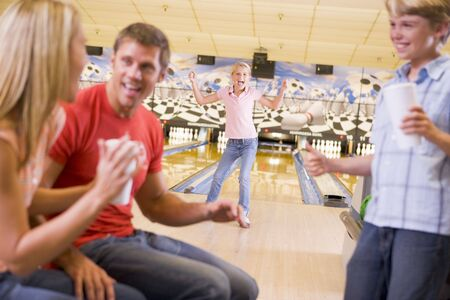 generation x: Family in bowling alley cheering and smiling Stock Photo