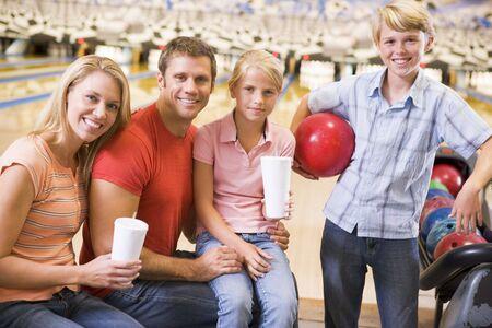 bolos: Familia en bolera con bebidas sonriente