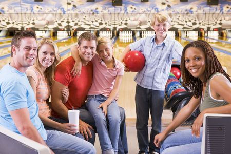 family and friends: Family in bowling alley with two friends smiling Stock Photo
