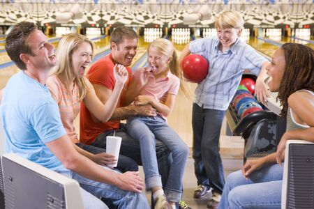 Family in bowling alley with two friends cheering and smiling photo