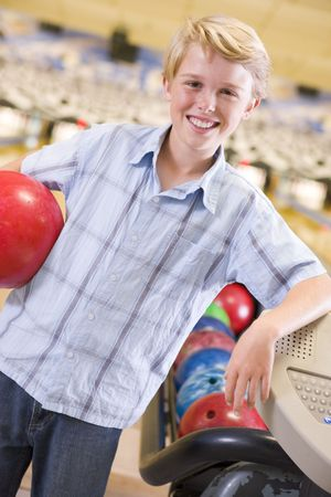 bowling alley: Young boy in bowling alley holding ball and smiling