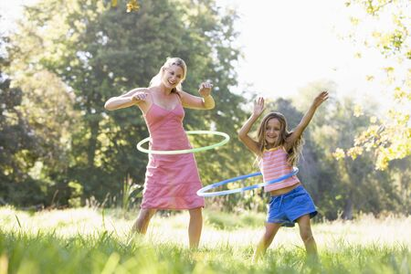 hoops: Woman and young girl outdoors using hula hoops and smiling Stock Photo