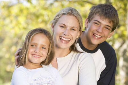 Woman with two young children outdoors smiling photo