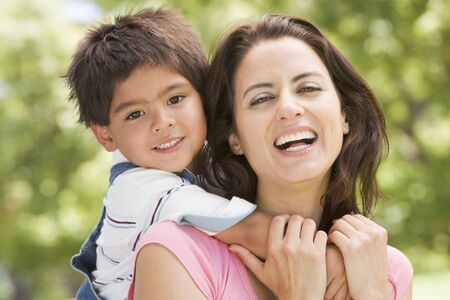 Woman and young boy outdoors embracing and smiling photo
