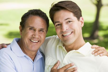 generation x: Two men outdoors embracing and smiling