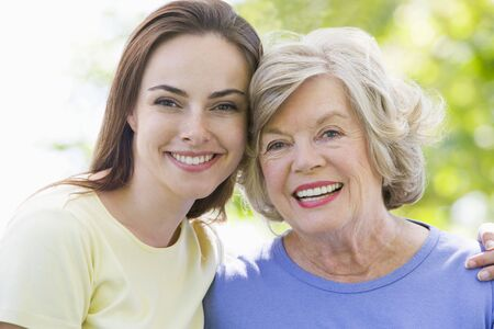 Two women outdoors embracing and smiling photo