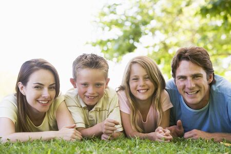 Family lying outdoors smiling photo