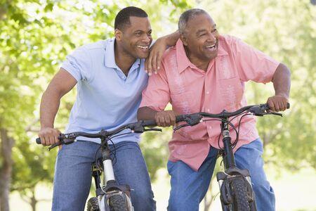 Two men on bikes outdoors smiling photo