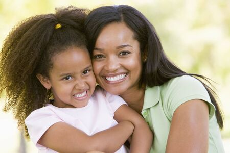 Woman and young girl outdoors embracing and smiling Stock Photo - 3475269
