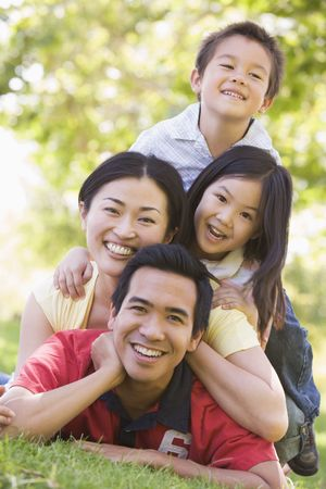 happy asian family: Family lying outdoors smiling