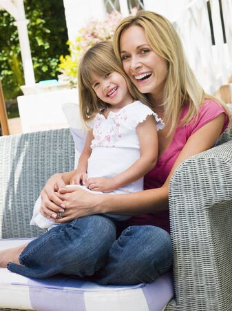 Woman and young girl sitting on patio laughing Stock Photo - 3475542