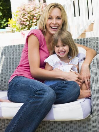 Woman and young girl sitting on patio laughing photo