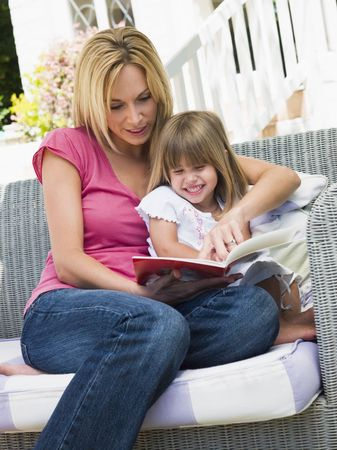 Woman and young girl sitting on patio reading book smiling photo