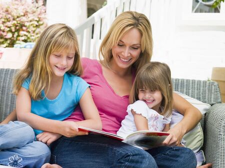 Woman and two young girls sitting on patio reading book smiling photo