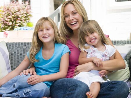 Woman and two young girls sitting on patio smiling Stock Photo - 3475522