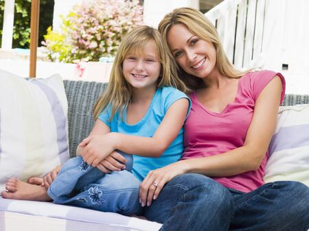 Woman and young girl sitting on patio smiling photo