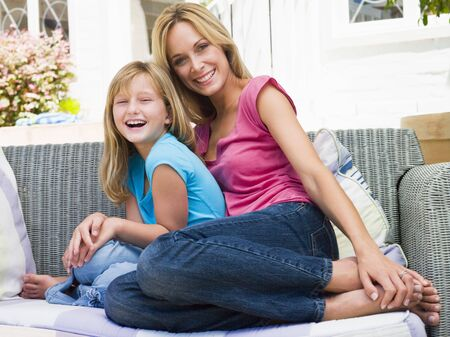 Woman and young girl sitting on patio smiling Stock Photo - 3475549