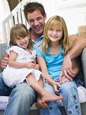 Man and two young girls sitting on patio smiling Stock Photo - 3475526