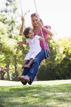 Woman and young girl outdoors on tree swing smiling Stock Photo - 3471611