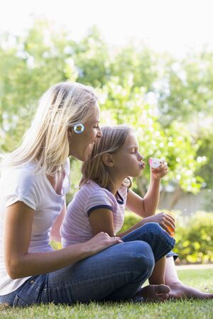 Woman and young girl outdoors blowing bubbles smiling photo